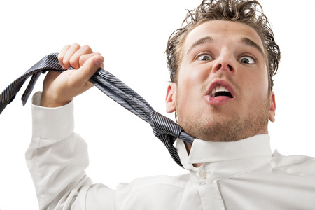 strangle: Young desperate business man with stress expression pulling his tie around neck.
