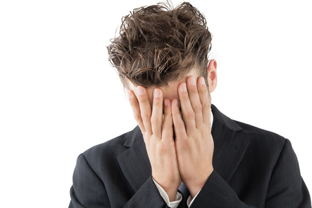 Desperate businessman in suit covering his face with hand.