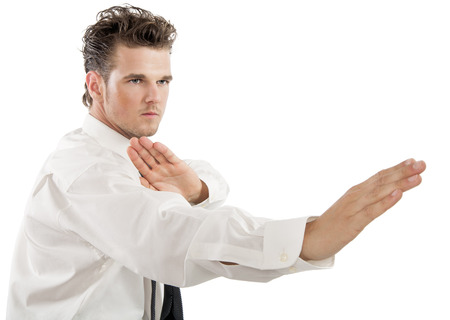 Serious young business man with karate fighting movements over white background. photo