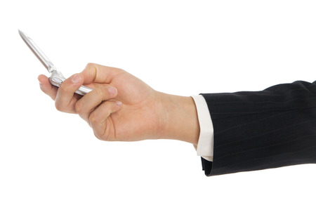 Male hand in business suit holding small mobile phone open and dialing. photo