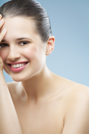 Beautiful smiling young natural woman with smooth glowing skin.