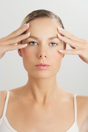 Elegante blanke vrouw doet gezichtsmassage bewegingen met de handen aanraken. Gezichtsmassage voor de huid en de onderliggende spieren. Natuurlijke verjonging technieken.
