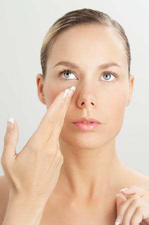 self help: Elegant Caucasian woman doing face massage movements with hands touching. Facial massage for skin and underlying muscles. Natural rejuvenation techniques.