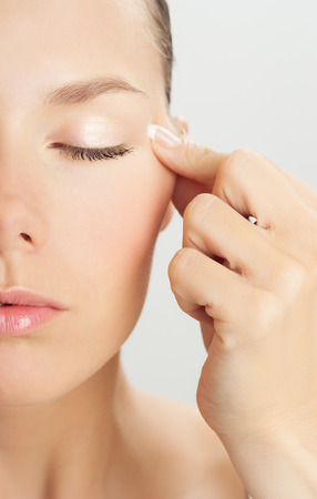 pinch: Elegant Caucasian woman doing face massage movements with hands touching. Facial massage for skin and underlying muscles. Natural rejuvenation techniques.