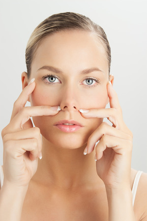 Elegant Caucasian woman doing face massage movements with hands touching. Facial massage for skin and underlying muscles. Natural rejuvenation techniques. photo