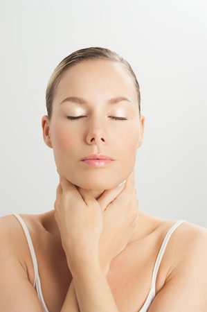 underlying: Elegant Caucasian woman doing face massage movements with hands touching. Facial massage for skin and underlying muscles. Natural rejuvenation techniques.