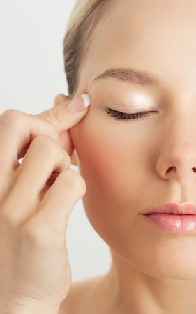 Elegant Caucasian woman doing face massage movements with hands touching. Facial massage for skin and underlying muscles. Natural rejuvenation techniques.