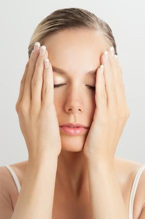 tratamiento facial: Mujer caucásica elegante haciendo movimientos cara de masaje con las manos tocando. Masaje facial para la piel y los músculos subyacentes. Técnicas de rejuvenecimiento natural. Foto de archivo