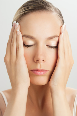 facial muscles: Elegant Caucasian woman doing face massage movements with hands touching. Facial massage for skin and underlying muscles. Natural rejuvenation techniques.