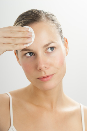 toner: Young beautiful woman cleansing face with toner on cotton disk. Makeup removal in skincare routine.