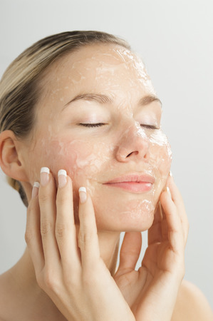 exfoliation: Closeup of young beautiful woman with gel exfoliation mask on face.
