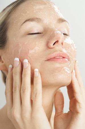 Close-up van jonge mooie vrouw met gel peeling masker op het gezicht. Stockfoto