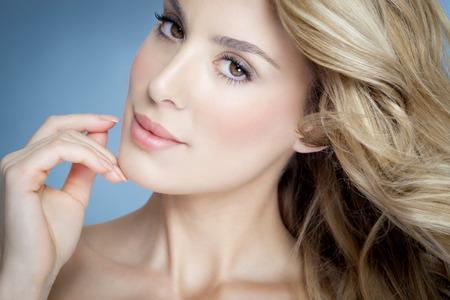 Close-up van de prachtige natuurlijke blonde vrouw met gloeiende huid over blauwe achtergrond.