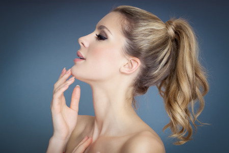 pony tail: Beautiful blond girl profile with pony tail over blue background.