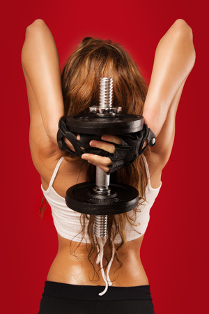 triceps: Young fit tanned Caucasian woman with long hair over red background. Stock Photo