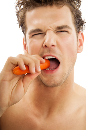vigorously: Young active Caucasian man vigorously biting a peeled carrot over white background. Healthy eating habits concept.
