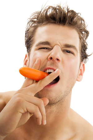 eating habits: Young active Caucasian man vigorously biting a peeled carrot over white background. Healthy eating habits concept.