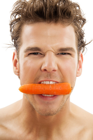 Young active Caucasian man vigorously biting a peeled carrot over white background. Healthy eating habits concept.