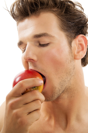 vigorously: Young active Caucasian man vigorously biting a red apple over white background. Healthy eating habits concept. Stock Photo