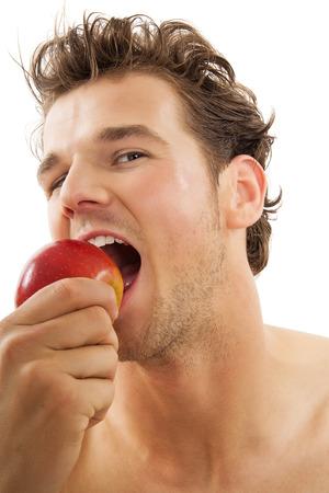 habitos saludables: Hombre caucásico activa joven que muerde con fuerza una manzana roja sobre fondo blanco. Concepto sano hábitos alimenticios.