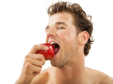eating habits: Young active Caucasian man vigorously biting a red apple over white background. Healthy eating habits concept. Stock Photo