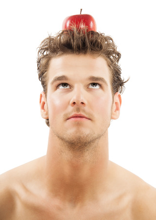 Young Caucasian man with red apple on top of head over white background. Eureka ideas and healthy eating concept. photo