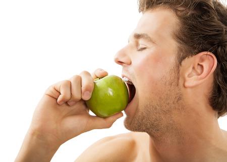 habitos saludables: Hombre caucásico activa joven que muerde con fuerza una manzana verde sobre fondo blanco. Concepto sano hábitos alimenticios.