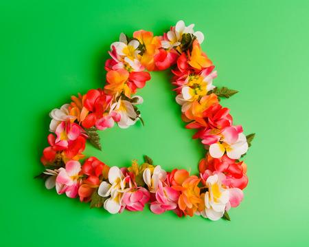 Heart shaped Hawaiian flower string over green background. Archivio Fotografico