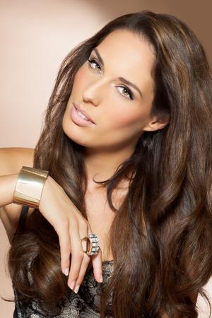 ojos marrones: Mujer hermosa con el pelo largo y oscuro. Belleza y concepto de moda en el estudio. Cerraduras brillantes de pelo preparado.