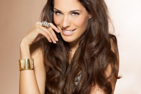 Mujer hermosa con el pelo largo y oscuro. Belleza y concepto de moda en el estudio. Cerraduras brillantes de pelo preparado.
