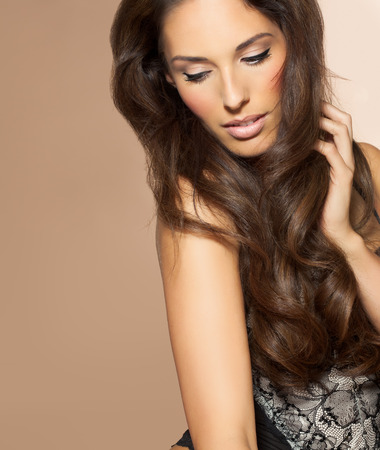 groomed: Beautiful woman with long dark hair. Beauty and fashion concept in studio. Shiny locks of groomed hair.