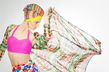 Fashion model wearing colorful style with bright pink top and silk robe with turban.