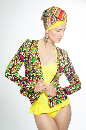 Exotic luxury style woman wearing turban and bright jacket.