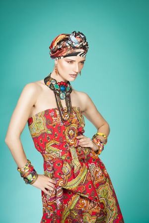 gypsy woman: Colorful exotic gypsy style fashion woman wearing red dress and turban over cyan background.