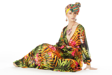 Colorful exotic gypsy style fashion woman wearing green silk dress and turban over white background. Banco de Imagens