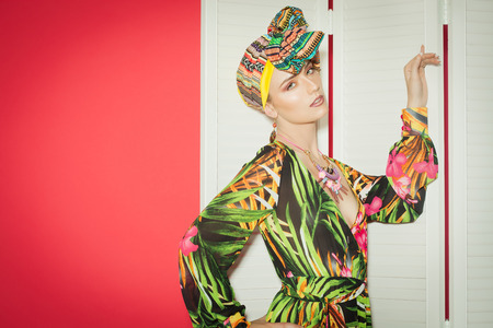 silk screen: Exotic colorful fashion style with Caucasian model over red background. Silk long hippie dress and turban.