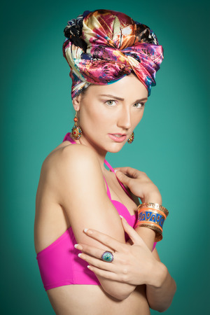 turban: Fashion model wearing colorful style with bright pink top and turban over cyan background.