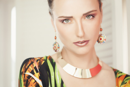 the seventies: Closeup of beautiful luxury seventies style fashion woman wearing earrings and golden necklace.