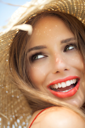 laughs: Young woman in straw hat smiling in summer outdoors. Stock Photo