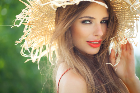 Young woman in straw hat smiling in summer outdoors. Banque d'images