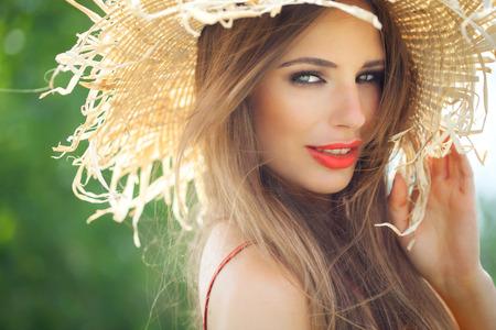 Jonge vrouw in strooien hoed glimlachend in de zomer buiten.