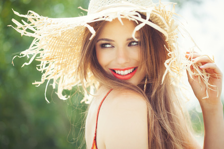 Young woman in straw hat smiling in summer outdoors. 스톡 콘텐츠
