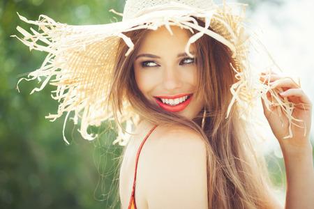 schöne augen: Junge Frau in Strohhut l�chelnd im Sommer im Freien.