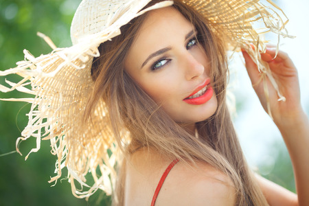 straw hat: Young woman in straw hat smiling in summer outdoors. Stock Photo