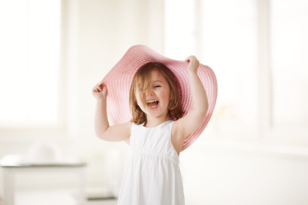 pink hat: Cute little girl playing indoors with large pink summer hat.