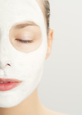 Closeup of beautiful young woman with white clay cosmetic mask. Skincare using masks. White clay clarifying facial mask.