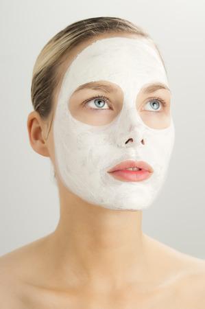 antifaz: Detalle de la hermosa mujer joven con la máscara cosmética arcilla blanca. Cuidado de la piel usando máscaras. Arcilla blanca aclarar máscara facial.