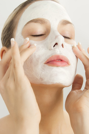 clarifying: Closeup of beautiful young woman with white clay cosmetic mask. Skincare using masks. White clay clarifying facial mask.