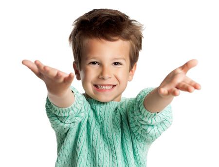 Muchacho de cinco años de edad europeo estilo que presenta sobre el fondo blanco del estudio. Muchacho con los brazos estiró en el gesto de bienvenida. Niño que mira entusiasmado.