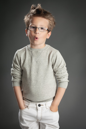 five year old: Handsome five year old boy posing in studio over gray background. Boy wearing reading glasses.